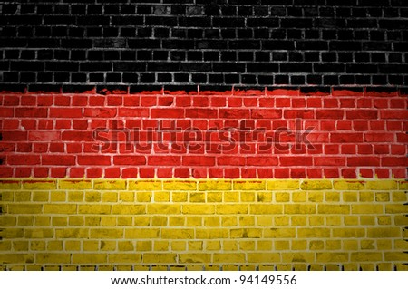 An image of the Germany flag painted on a brick wall in an urban location