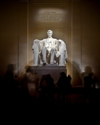 An image of the Lincoln Memorial taken at night.  Tourist move and gather around the monument.