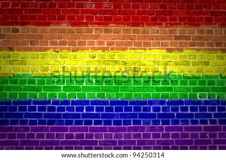 An image of the Rainbow flag painted on a brick wall in an urban location