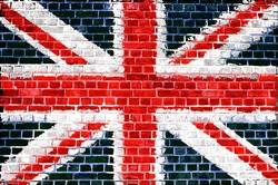 An image of the union jack flag painted on a brick wall in an urban location