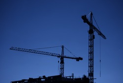 An image of two construction cranes silhouetted against a dark evening sky on a city centre building site.