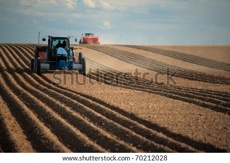 An image of two Tractors planting potatoes in the fertile farm fields of idaho.