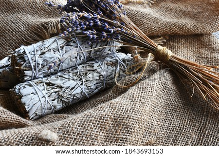 An image of white sage smudge sticks and dried lavender flowers on vintage burlap cloth.  Stock photo ©