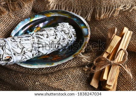 An image of white sage smudge sticks in an abalone shell with a burlap background.  Stock photo ©