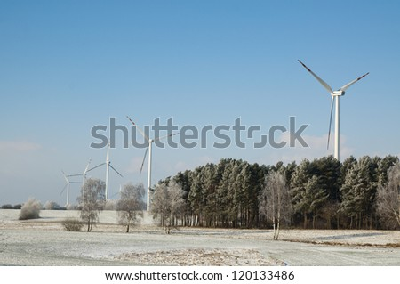 An image of winter scenery with windturbines in the background