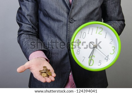 An image of young businessmen holding money and watch in his hands