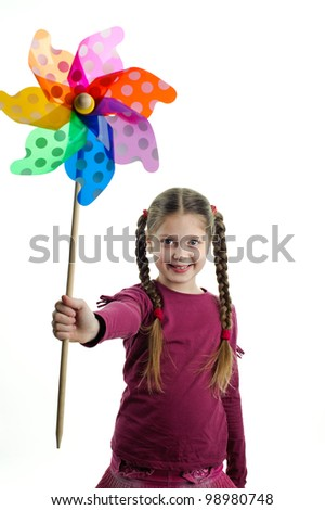An image of young cute girl holding a wind toy
