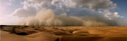 An image showing a severe sandstorm of high altitude with cumulonimbus rain clouds forming near towering mountains heading towards a sandy desert.