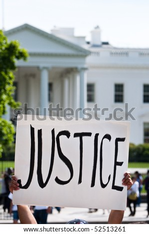 """An immigration reform activist holds a sign reading """"Justice"""" during a protest at the White House in Washington, DC."""