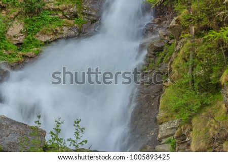 an imposing waterfall falls impetuous from the glaciers in the National Park of Great Paradise,in Piedmont,Italy #1005893425