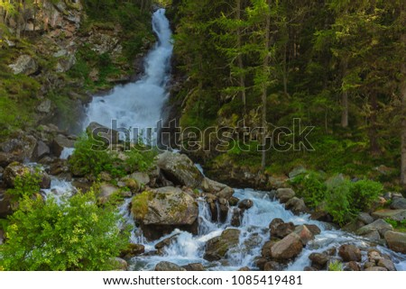 an imposing waterfall flows impetuously in the midst of  alpine vegetation /a deafening waterrfall falling from glaciers in the National Park of Great Paradise,in Piedmont,Italy. #1085419481