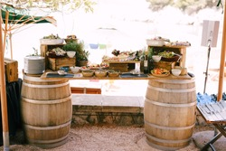 An impromptu table of two wine barrels and a wooden bar with delicacies and flowers.