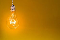 An incandescent electric lamp without a cartridge is hanging on a wire. Yellow background.