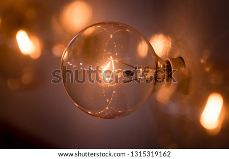 An incandescent light warmly glows.  Reminiscent of a vintage sign, you can see the glowing filament surrounded by soft focus and bokeh. Shot behind-the-scenes of a television production.  #1315319162