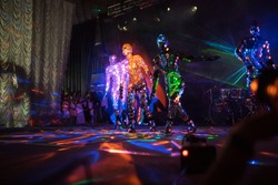 an incredible beauty of the performance of artists and dancers on stage, a fireshow with LED suits and lasers reflecting on a lot of mirror details in clothes, iridescent with all the colors