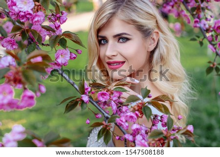An incredible, delicate blonde in a luxurious, delicately blue dress walks in the spring, sakura and cherry orchards are in bloom. Princess with long curly hair. Vanilla color art photo #1547508188