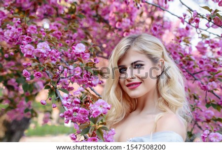 An incredible, delicate blonde in a luxurious, delicately blue dress walks in the spring, sakura and cherry orchards are in bloom. Princess with long curly hair. Vanilla color art photo #1547508200