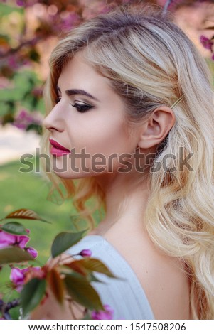An incredible, delicate blonde in a luxurious, delicately blue dress walks in the spring, sakura and cherry orchards are in bloom. Princess with long curly hair. Vanilla color art photo #1547508206