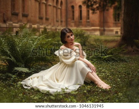 An incredibly beautiful princess sits in the castle garden amid the fern and moss. A beautifully childish face and collected hair is a neat hairdo. On the lady is a vintage ivory dress. Art Photo