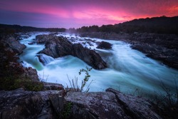 An incredibly vibrant pink and purple sunrise over the Potomac River at Great Falls Park during a late October morning.