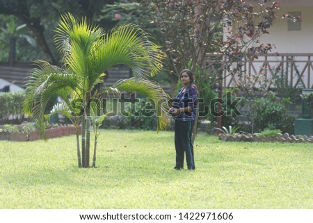 An Indian Bengali beautiful brunette woman in casual blue checkered top and black trouser is standing casually in  front of a tree  in a park surrounded by the trees. Indian lifestyle.