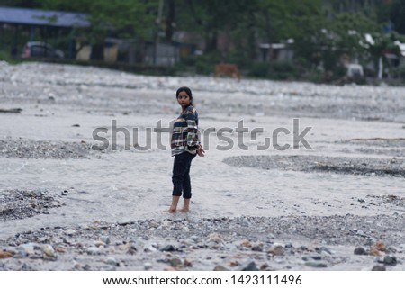 An Indian Bengali beautiful brunette woman in casual top and blue jeans is standing casually in a dry river bed surrounded by the trees on a summer day. Indian lifestyle.