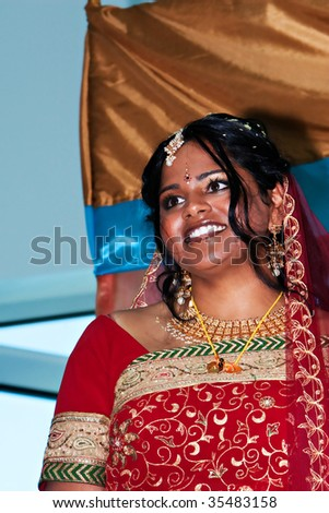 An indian bride in a red sari smiles