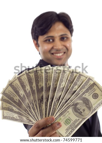 An Indian business man holding a handful of money isolated over white