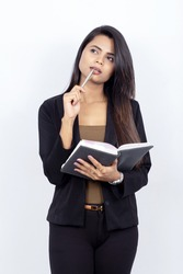 an Indian businesswoman on white background holding a pen and an open notebook - thinking and ideating