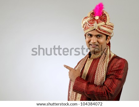 An Indian groom wearing the traditional sherwani attire. - stock photo