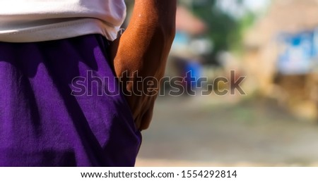 An Indian guy standing against a blurry background on a sunny day. A young Indian guy standing on the road and his left hand is under a pocket of his sports pant.