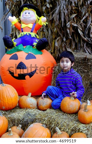An indian kid having fun with the haloween pumpkins