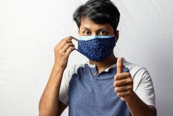 An Indian man shows thumbs up to double masking during covid-19 pandemic, healthcare concept