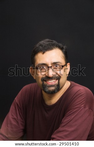 An Indian man with a beard against a black background