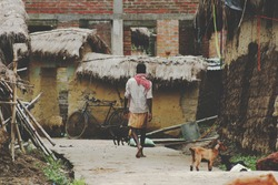 An Indian or asian farmer walking on the street against a clay and bricks house background.Cycle,wearing a lungi and gamcha. Village scene. Copy space.