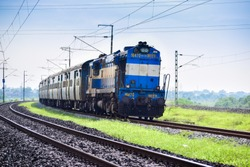An Indian Railways Diesel Locomotive of type WDM3A accelerating hard and passes through a curved track after a scheduled halt at a suburb station.