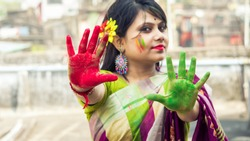 An Indian woman dressed in saree, celebrating Holi with colors on her hands and face - Holi concept (selective focus on hand)