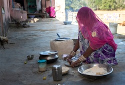 an indian woman making food for family in rajasthan, india