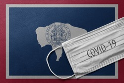 An individual face medical surgical mask on Wyoming State Flag Background. Health mask. Protection against COVID-19 virus, influenza, SARS. Coronavirus in Wyoming