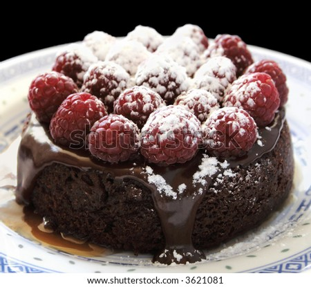 an individual-sized chocolate cake topped with ganache, fresh raspberries, powdered sugar and caramel sauce