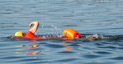 An individual swimmer is training in the bay wearing a red top, yellow bathing cap and an orange safety flotation device.