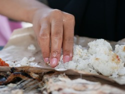 An Indonesian woman eating her meals using her bare right hand, a common practice and considered a better way of eating for most Indonesian traditionally. Eating seafood. Eating rice.