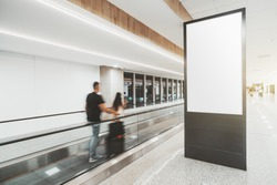 An indoor arrival or departure area of a modern airport with blurry silhouettes of  passengers passing by on travelator and a vertical empty mockup of an information LCD panel or an advert billboard