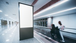 An indoor arrival or departure area of an airport with motion blurred silhouettes of passengers passing by on travelator and a vertical empty mockup of an information LCD panel or an advert billboard