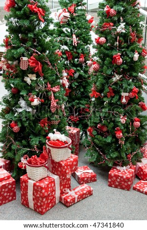 An indoor Christmas display with decorated trees and packages.