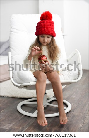 An indoor portrait of a cute little girl in a knitted warm red cap holding Christmas decorations - a photo representing a concept of waiting for Christmas