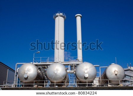An industrial plant with silver tanks with smokestacks