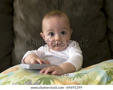 An infant child plays with a remote control