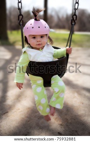 An infant in a playground swing with a protective helmet