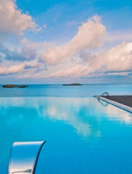 An infinity pool in front of the sea under impressive clouds with inox jet water and waterfall.